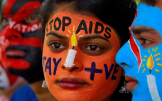 woman in face paint that reads stop aids